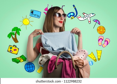 young girl in sunglasses measures clothes from a bag full of clothes on a light background with painted tourist icons. Concept fold clothes before the trip.