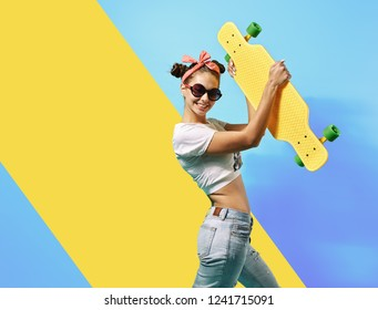 Young girl in sunglasses and pink bow on her head dressed in jeans and top stands with yellow skateboard on the back on the blue background in the studio