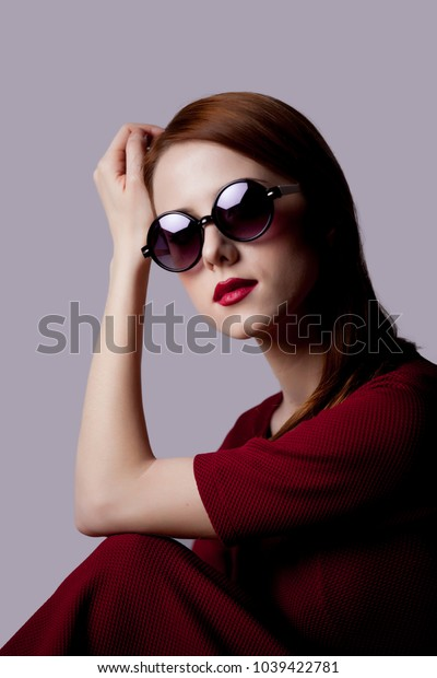 Young girl with sunglasses in red dress on grey backgorund