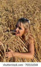 Young girl in sunglasses  in a wheat field with ears