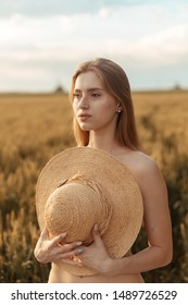 young young girl in a sunset field with a straw hat