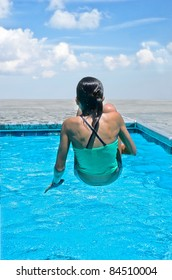 Young girl suspended over the water in a swimming pool.