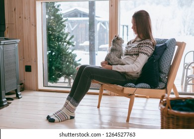 Young girl in sweater with cat relaxing on chair in log cabin near big window