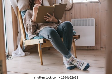 Young girl in sweater reading book and relaxing on chair in log cabin near electric heater