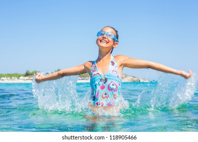 Young girl in swimming goggles playing in the wave with spray