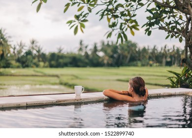 Young girl swimming in infinity pool with a view on rice terrace. Travelling to Ubud, Bali.