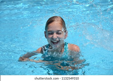 young girl in swimming pool splashing and smiling summer vacation