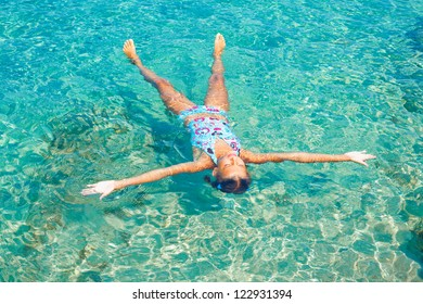 Young girl swimming in the transparent sea