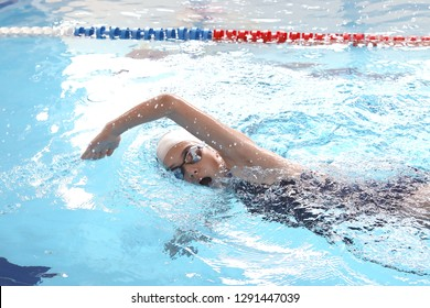 young girl swims freestyle in the pool