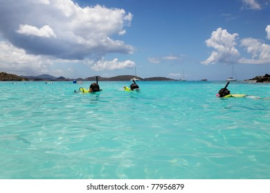 Young girl swims to her Dad and brother, snorkeling in St. John