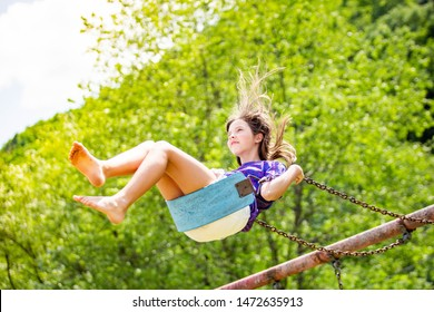Young girl swinging high bright summer day alone