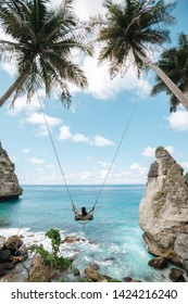Young girl swinging on a swing overlooking the blue sea. Travel adventure on paradise tropical island. A young girl swinging on a swing between palm trees on the beach of a tropical island
