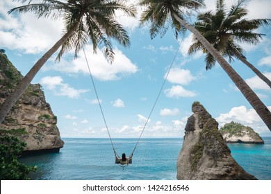 A young girl swinging on a swing between palm trees on the beach of a tropical island. Young woman watching the ocean on a sunny day. Sunny summer day in paradise