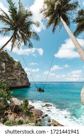 Young girl swinging on a swing overlooking the blue sea. Travel adventure on paradise tropical island Nusa Penida. A young girl swinging on a swing between palm trees on the beach of a tropical island