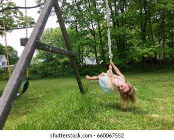 Young girl swinging upside down on rope swing