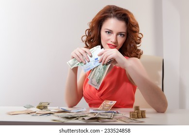 young girl at  table with greedy counts money lying on  table and looking at  camera
