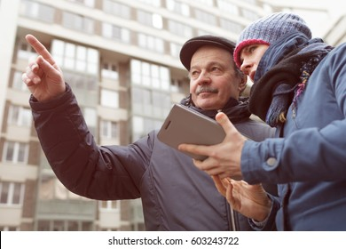 A young girl with a tablet in her hands asks for directions from a stranger. He shows her  with finger the right direction