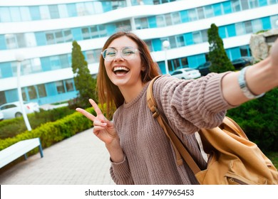 Young girl take selfie from hands with phone on summer spring city street. Urban life concept.Closeup selfie-portrait student of attractive girl in sunglasses with long hairstyle and snow-white smile