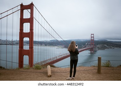A young girl takes a photo of the golden gate bridge with her phone on an overcast day
