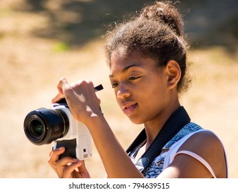 young girl takes a photograph with a camera