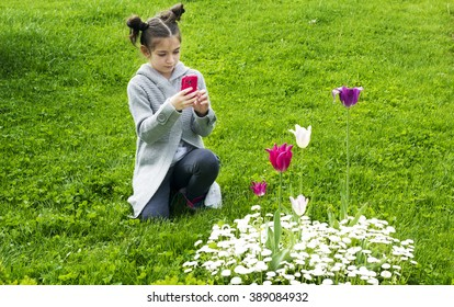 Young girl takes a picture with a phone of spring flowers