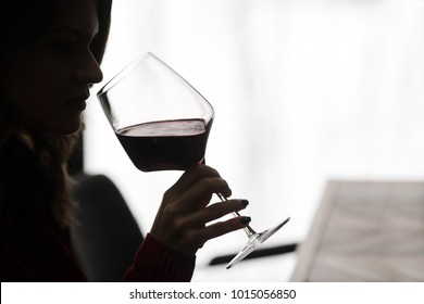 A young girl takes a sip of red wine in a restaurant