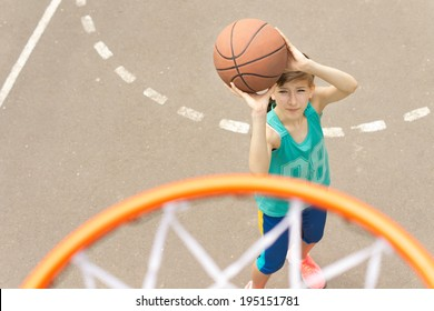 Young girl taking aim at the goal on a basketball court standing with the ball raised aiming at the hoop, view from above