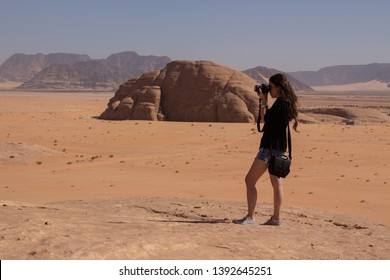 Young girl is taking a photo in the desert Wadi Rum in Jordan place of Lawrence of Arabia surrounded by sand and rocks martian place