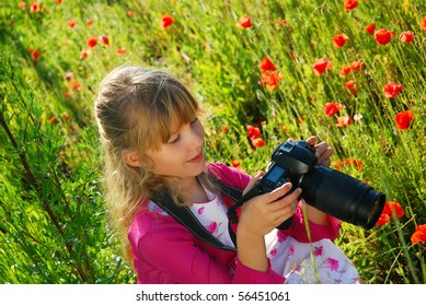 young girl taking photo of poppies on the meadow by professional camera