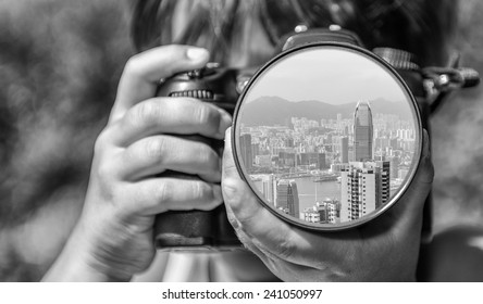 Young girl taking photos of Hong Kong skyline by professional digital camera.