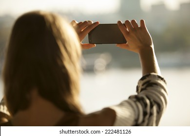Young Girl Taking Photos Of Landscape With Mobile Smart Phone