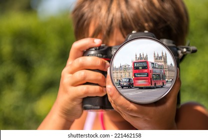 Young girl taking photos of London Bus by professional digital camera.