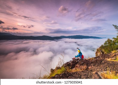 Young girl are taking photos  the sea of mist on high mountain in Nakornchoom, Phitsanulok province, Thailand.