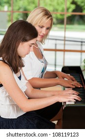 Young girl taking piano lessons from a teacher