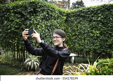 young Girl taking picture self portrait on smart-phone in garden