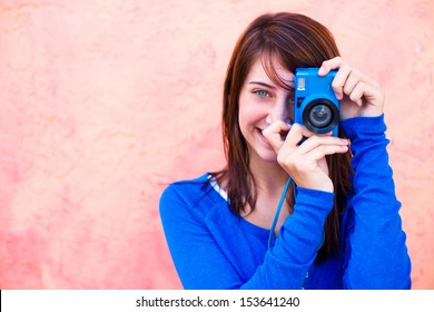 Young girl taking picture through digital camera. Horizontal shot.