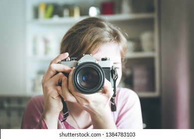 Young girl is taking a picture with a vintage camera