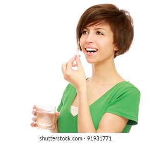 A young girl taking pills, isolated on white background