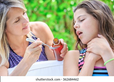 young girl taking a spoonful of syrup of her mother hand