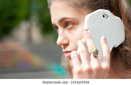 Young girl talking by smartphone