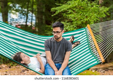 A young girl is talking to her older brother in a green hammock