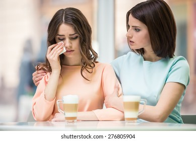Young girl talking with her upset friend and holding her shoulders in cafe.