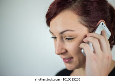 A young girl talking on a cell phone with a smile on her face, a white background, facial expressions