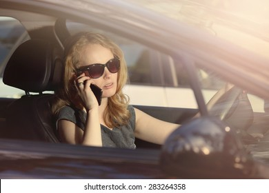 Young girl talking on the phone in the car