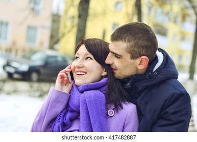 young girl talking on the phone,laughing with a young man