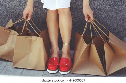 young girl with tanned slim legs in red patent leather shoes and a lot of brown paper bags her hands. Shopaholic woman in the city. The concept of shopping, sales and purchases of things.