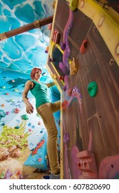 Young girl with tattoos scrambles and poses on a children's climbing wall