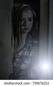 A young girl in tears with a flashlight peeking out of the dark room.