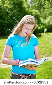 Young girl teenager reading books outdoors on grass in summer day
