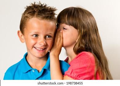 Una joven que le dice un secreto a un niño. Aislado sobre fondo blanco.